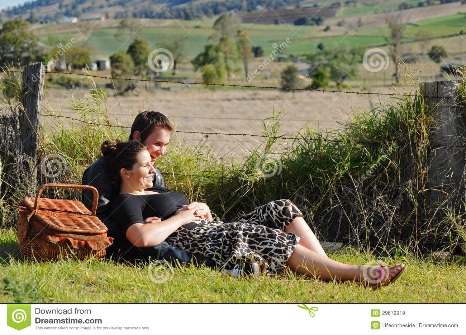 Amantes jovenes felices que ríen y que sonríen al aire libre
