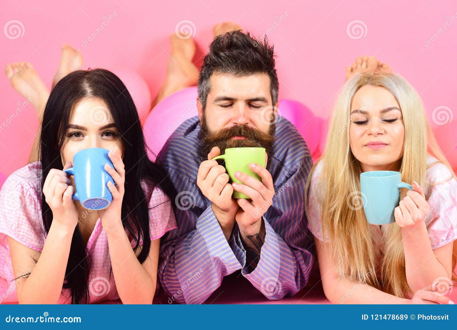 Amantes no café da bebida do amor na cama O Threesome relaxa na manhã com café Conceito dos amantes Homem e mulheres em doméstico
