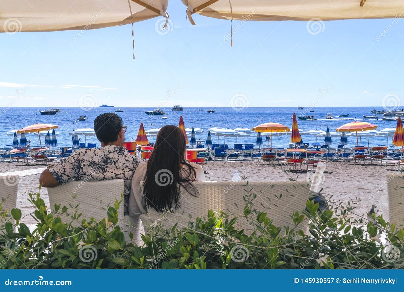 Amantes que se sientan, mirando en el cielo y el mar, mountion, debajo del paraguas de sol Vacaciones, turismo, hooneymoon Muchac