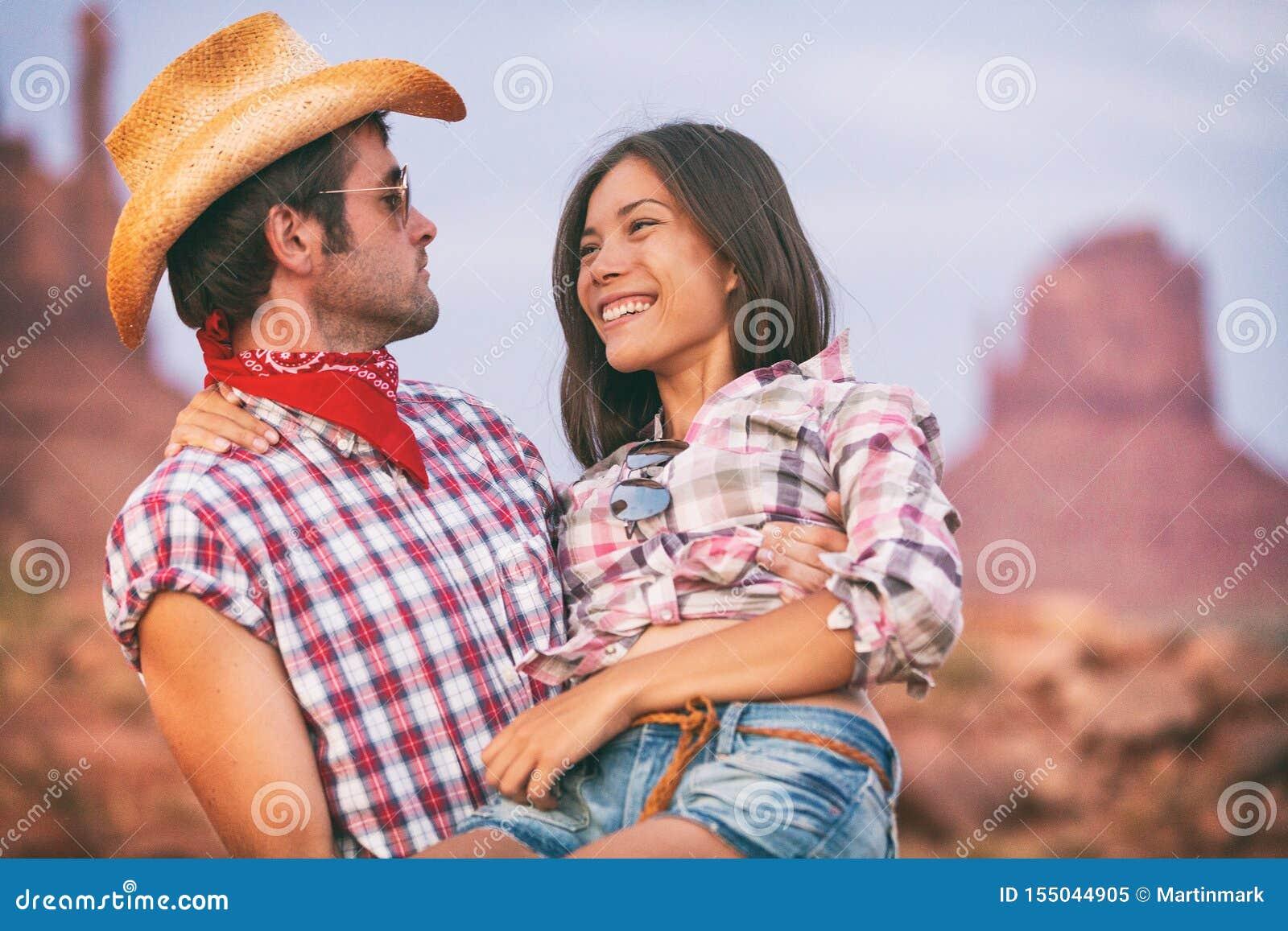 Amanti cowboy e cowgirl nelle coppie sveglie di amore nel paesaggio remoto di U.S.A. Cappello da cowboy d uso del ragazzo che por