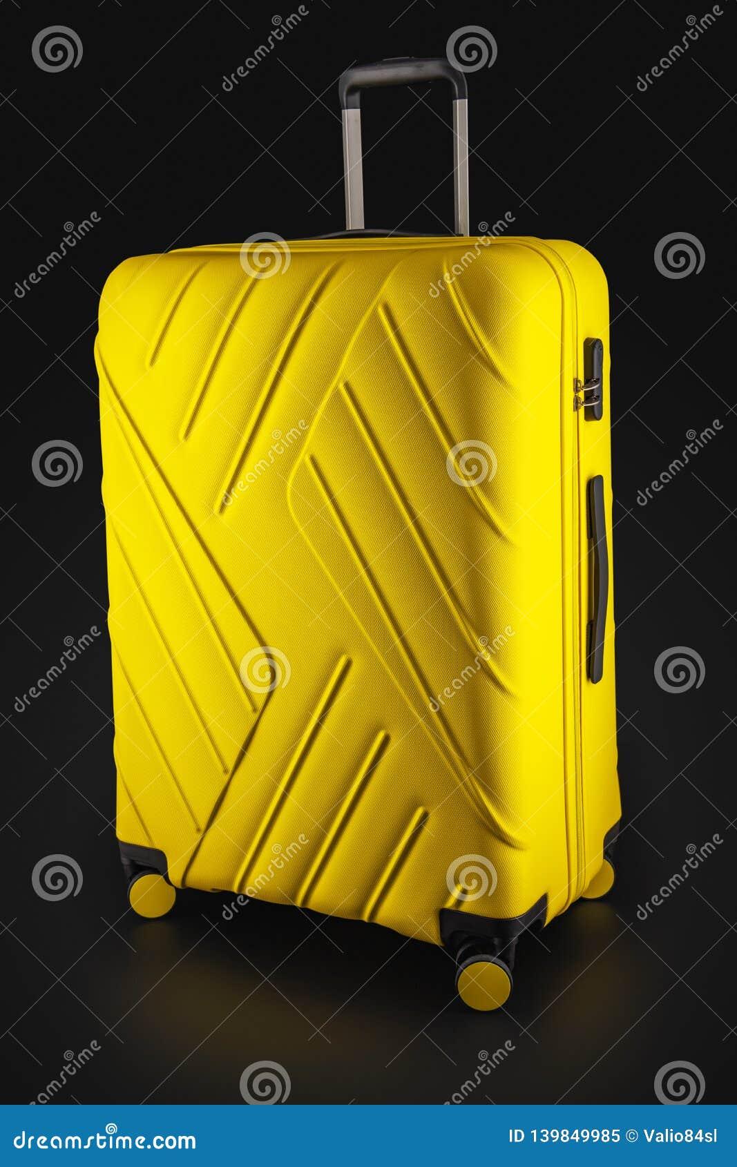 Amarillo de la maleta con el equipaje para el vuelo aislado en el fondo negro, trayectoria de recortes
