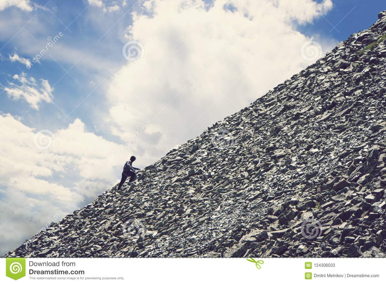 Amateur mountaineering against the blue sky with clouds. Man climbing up hill to reach the peak of the mountain. Persistence, dete