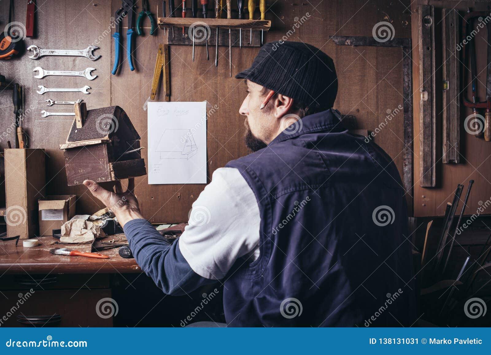 Amateurtischler mit hölzernem Vogelhaus