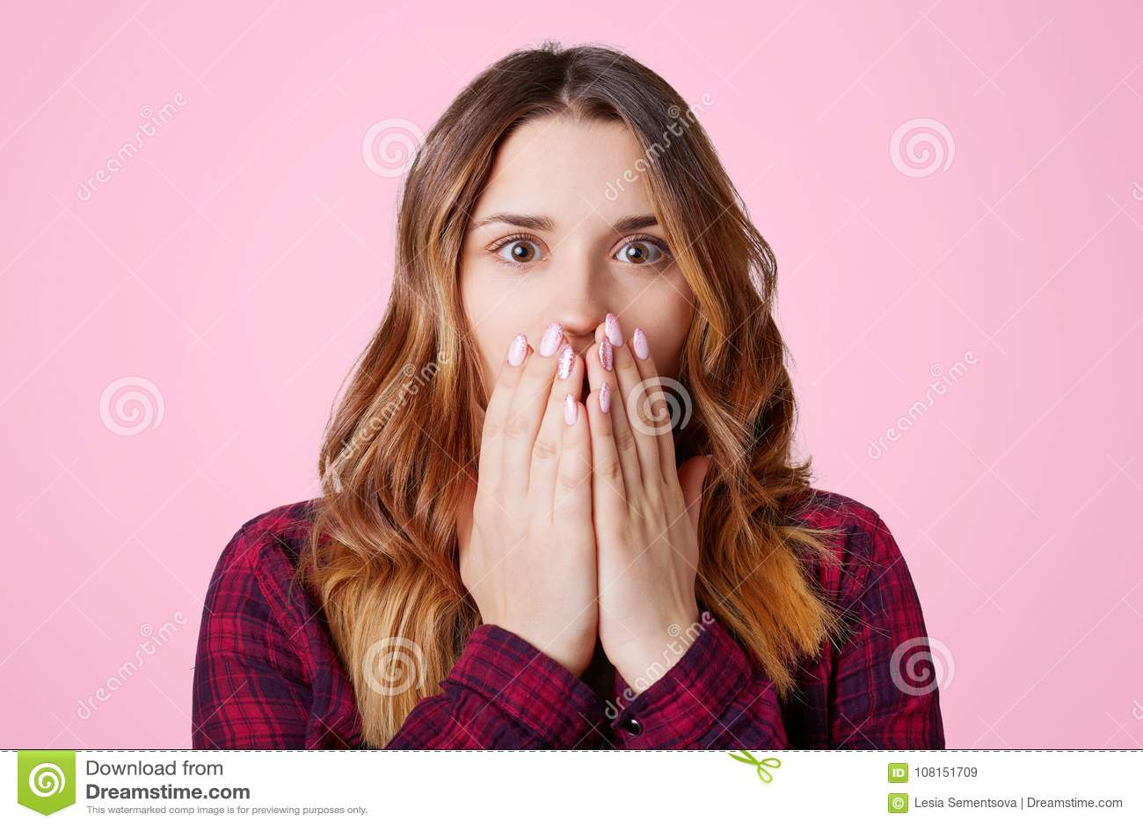 Amazed вспугнуло женщину детенышей довольно одетую в checkered рубашке, покрывает рот с руками, сотрясаемый для того чтобы получи