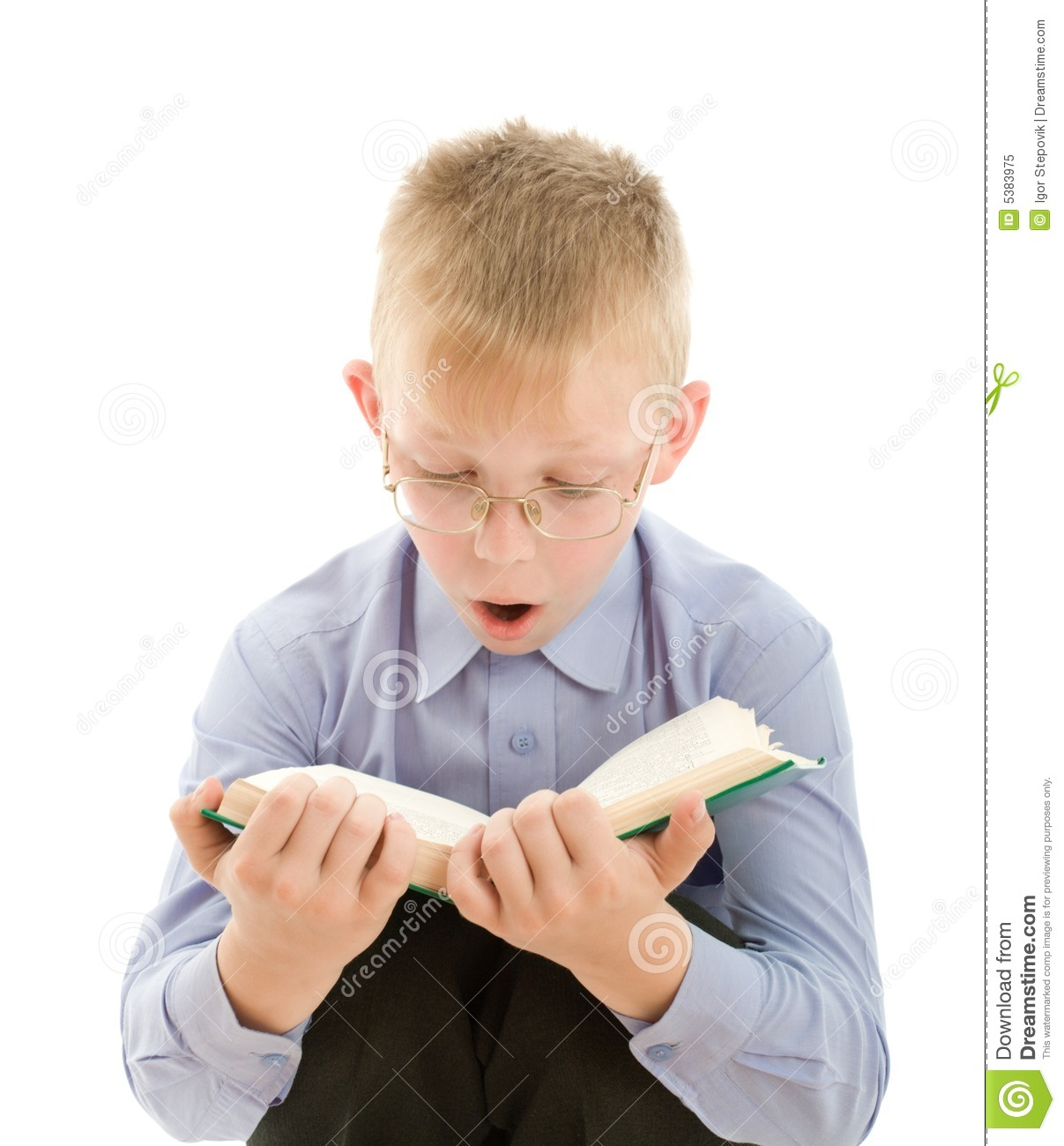 Portrait of amazed boy in eyeglasses reading very interesting book ...