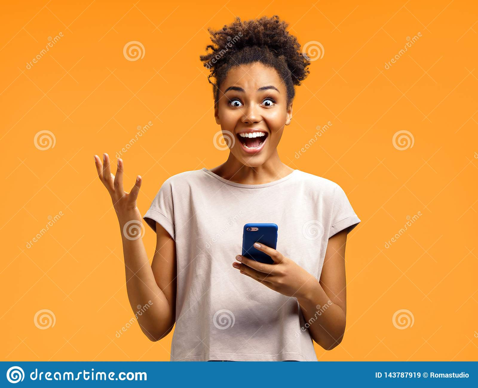 Amazed girl holds smartphone, happy to receive notification, gestures actively from happiness.