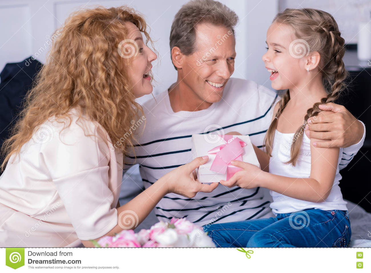 Amazed Little Girl Getting A Birthday Gift From Her Grandparents