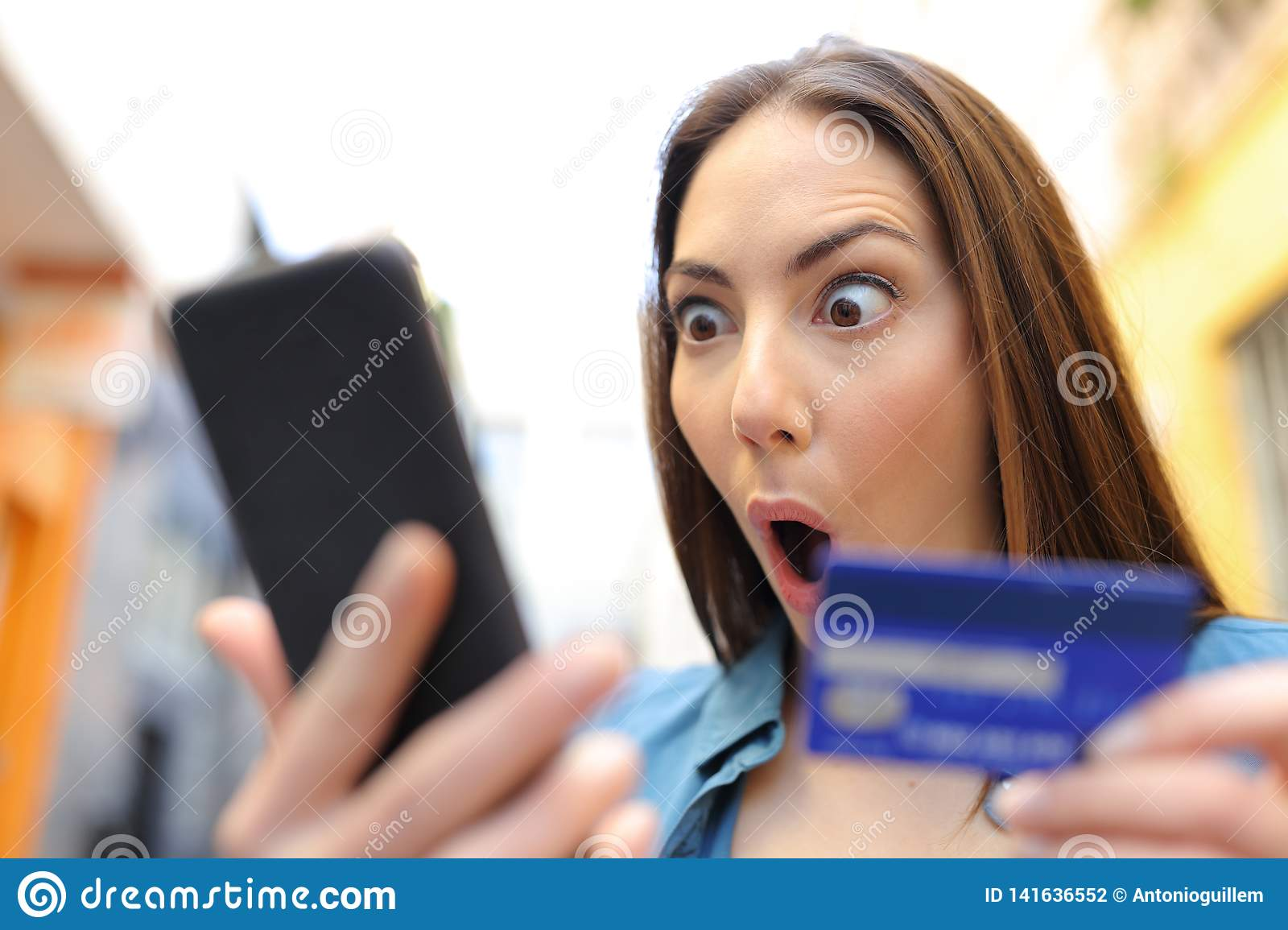 Amazed woman buying with credit card finding discount