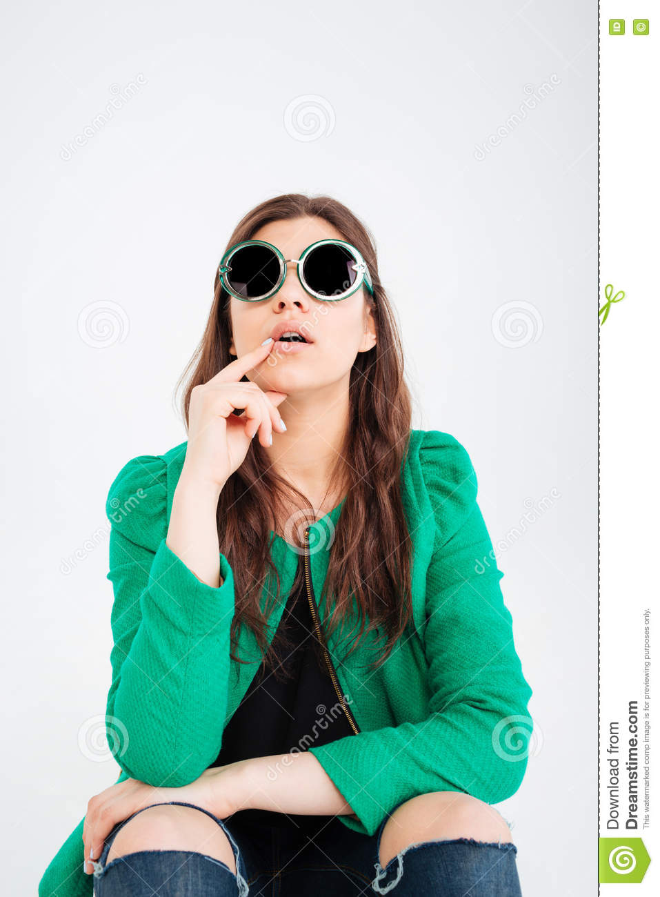 Amazed woman in round sunglasses sitting and looking up