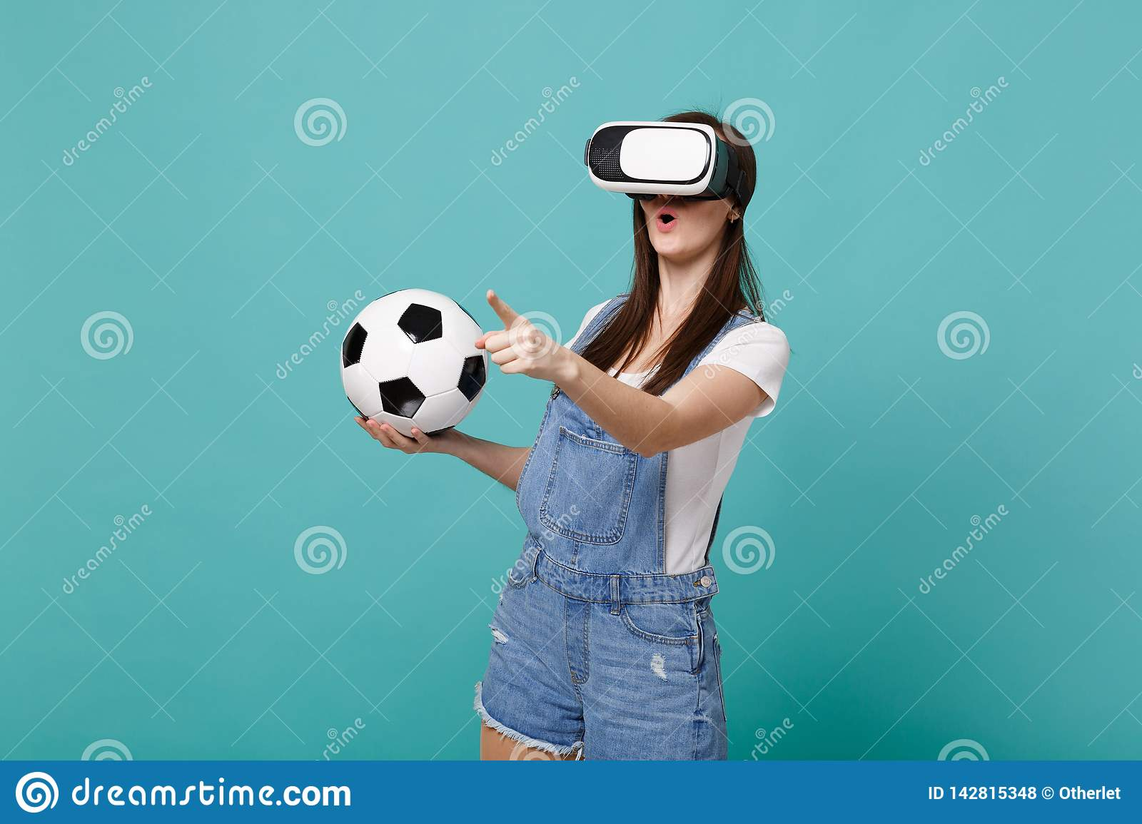 Amazed young girl football fan looking in headset holding soccer ball playing touch something like push click on button