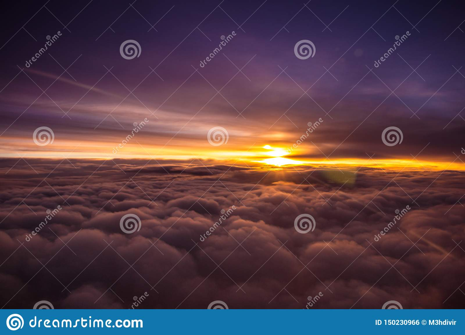 Amazing and beautiful sunset above the clouds with dramatic clouds