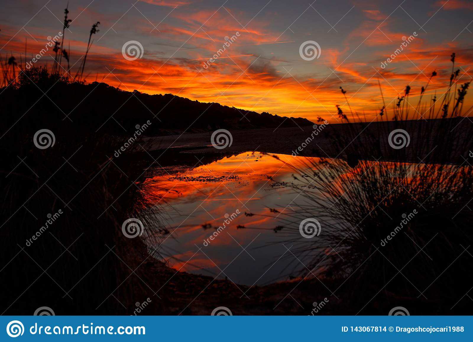 Amazing blazing sunset landscape over the island and the sky above it with an awesome sun. sunset view on the beach