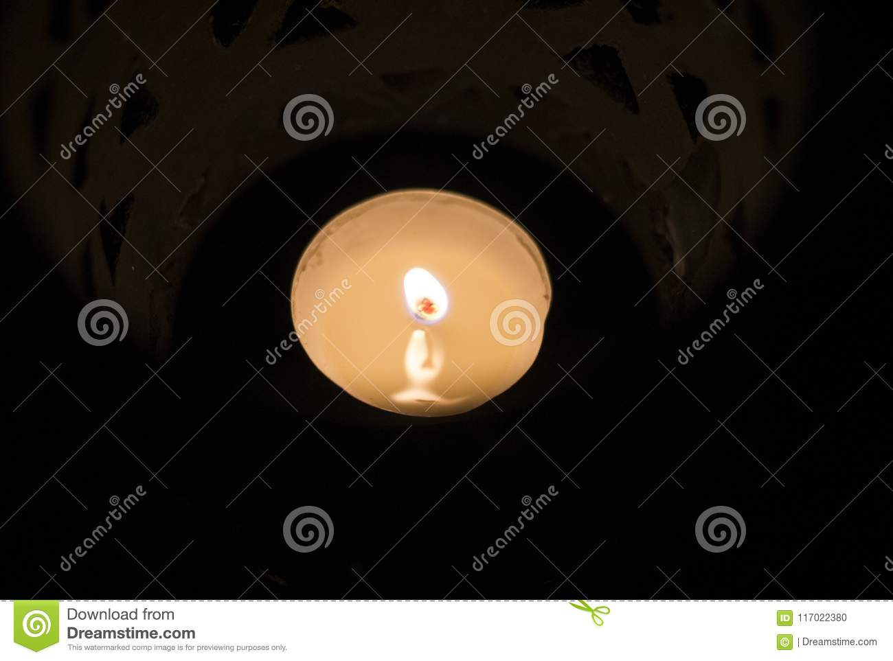 Amazing close up of lit candles in a beautiful blue candle holder