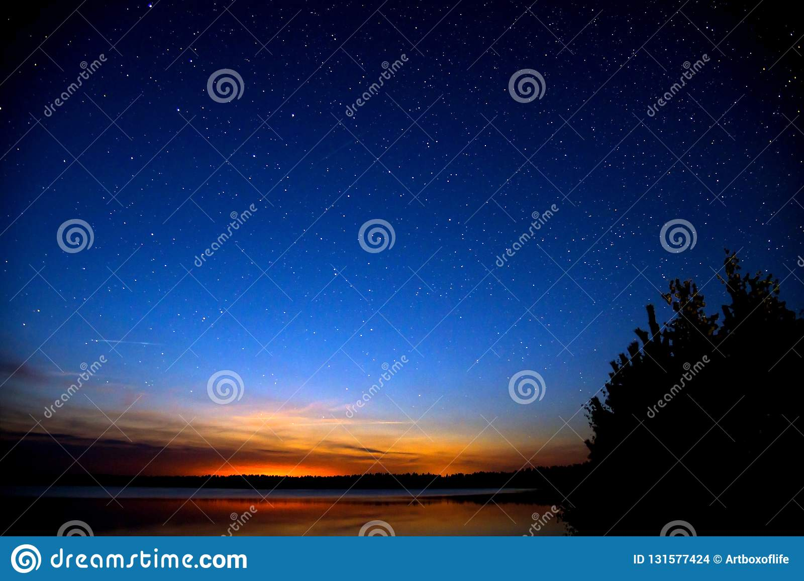 Amazing colorful sky after sunset by the river. Sunset and night sky with a lot of stars