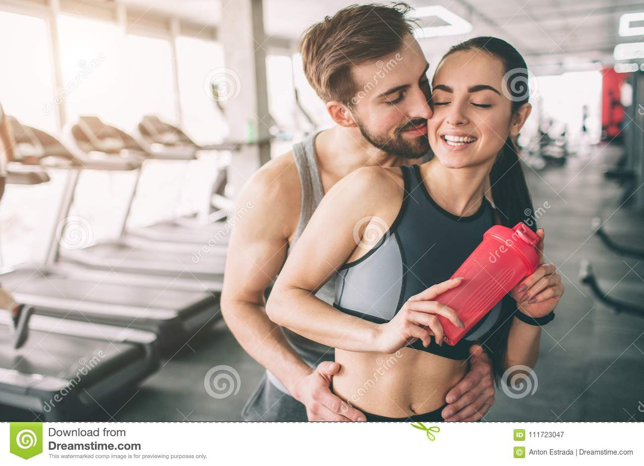 Amazing couple standing in the gym. The guy is hugging his girlfriend. She looks happy. Close up. Cut view.