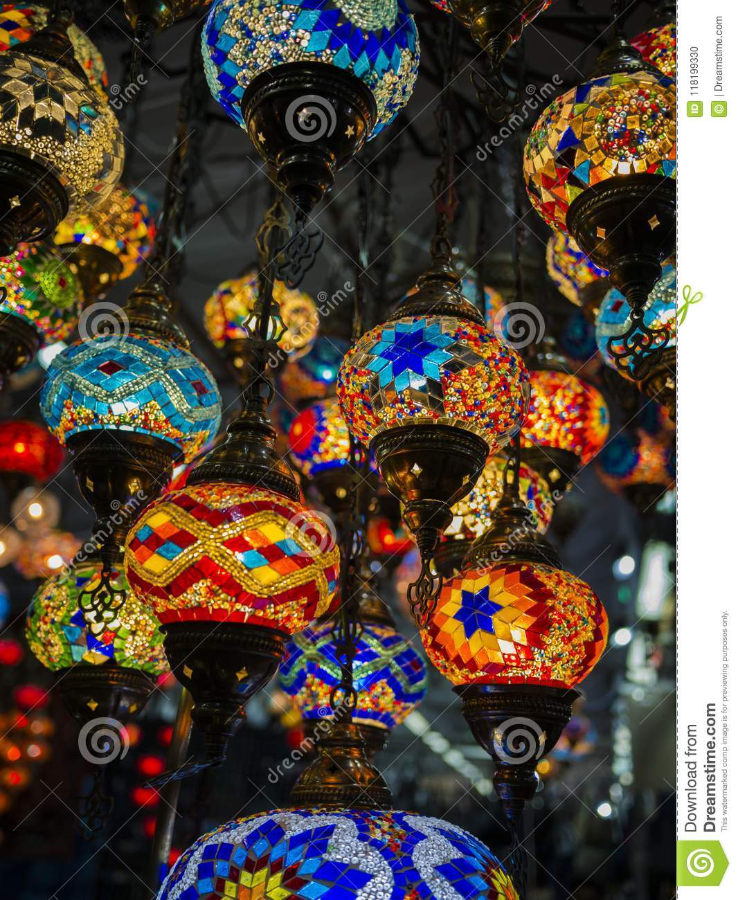 Amazing and elegant photo of ornate and colourful Turkish lights hanging from the ceiling.