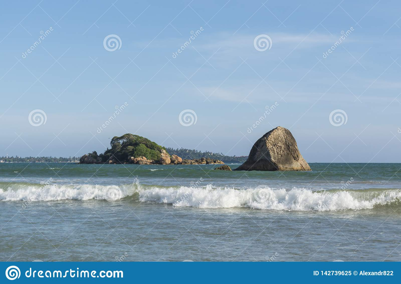 Amazing landscape of the ocean on beautiful tropical beach with rocks in Weligama town