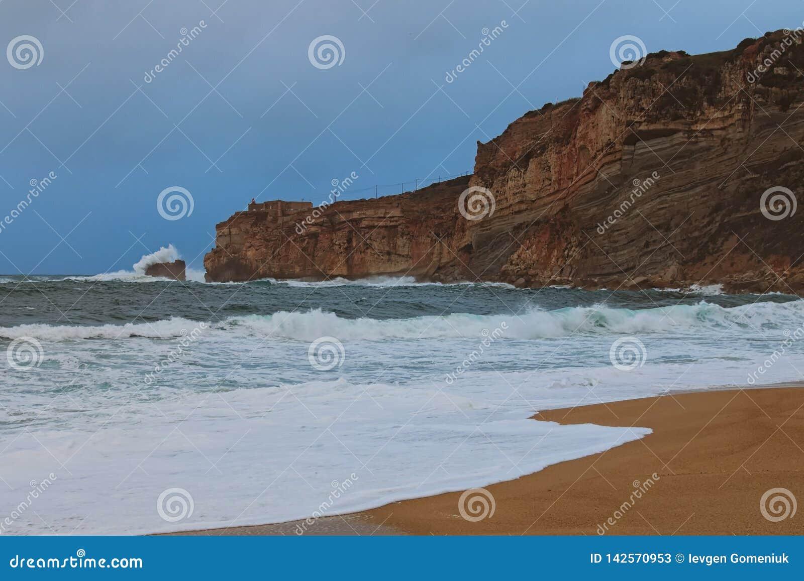 Amazing landscape view of stormy Atlantic ocean near famous touristic city Nazare. Big wave breaks about picturesque cliff