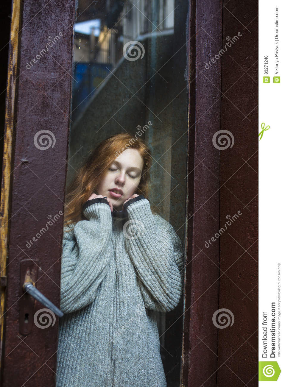 Amazing Redhead Model With Freckles Behind The Old Glass Door Stock