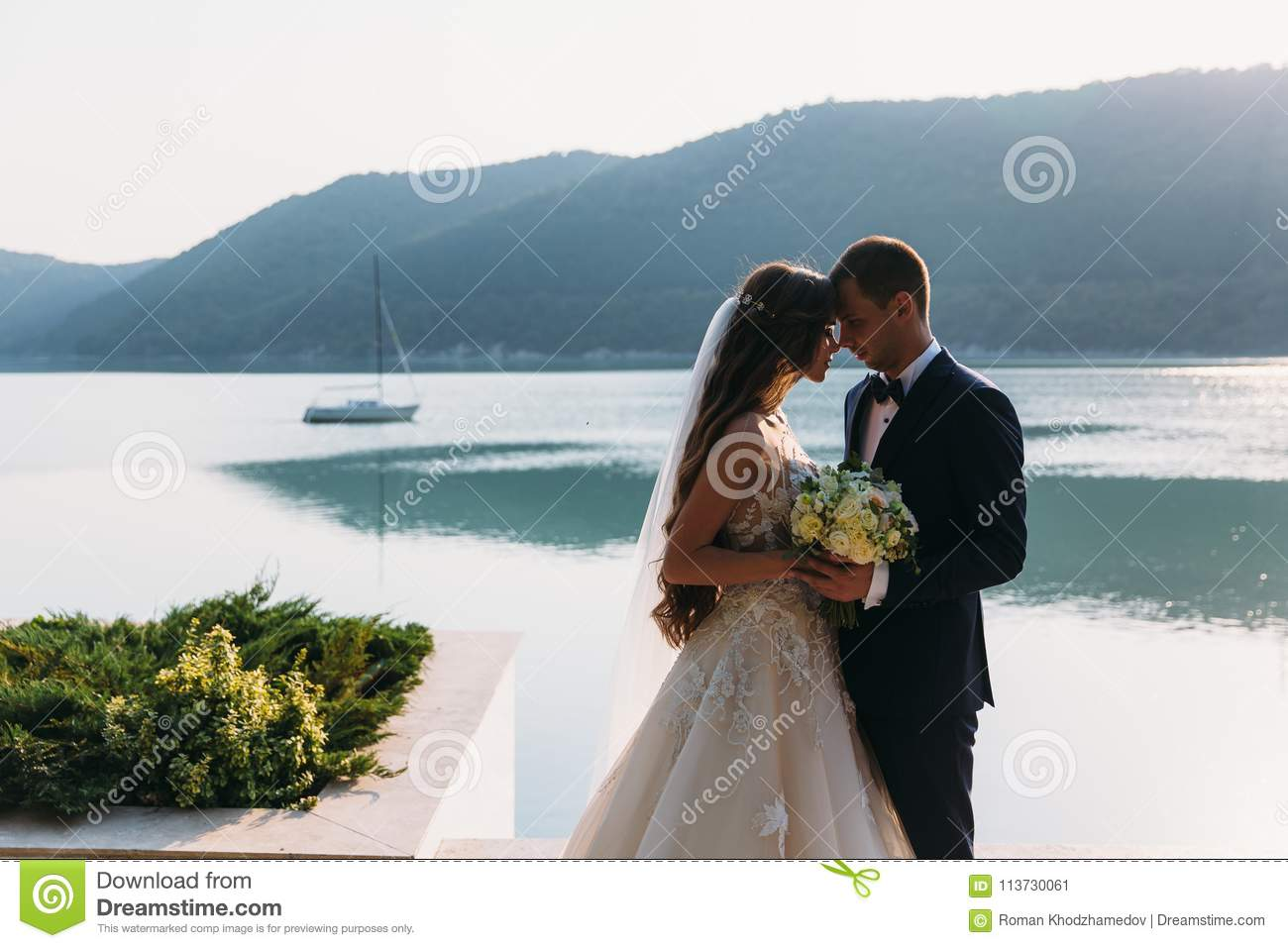 Amazing Wedding Couple, Bride And Groom Holding Hands On A Lake ...