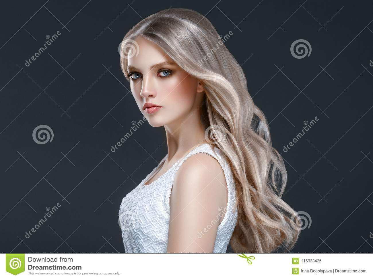 Amazing woman portrait. Beautiful girl with long wavy hair. Blonde model with hairstyle over black background