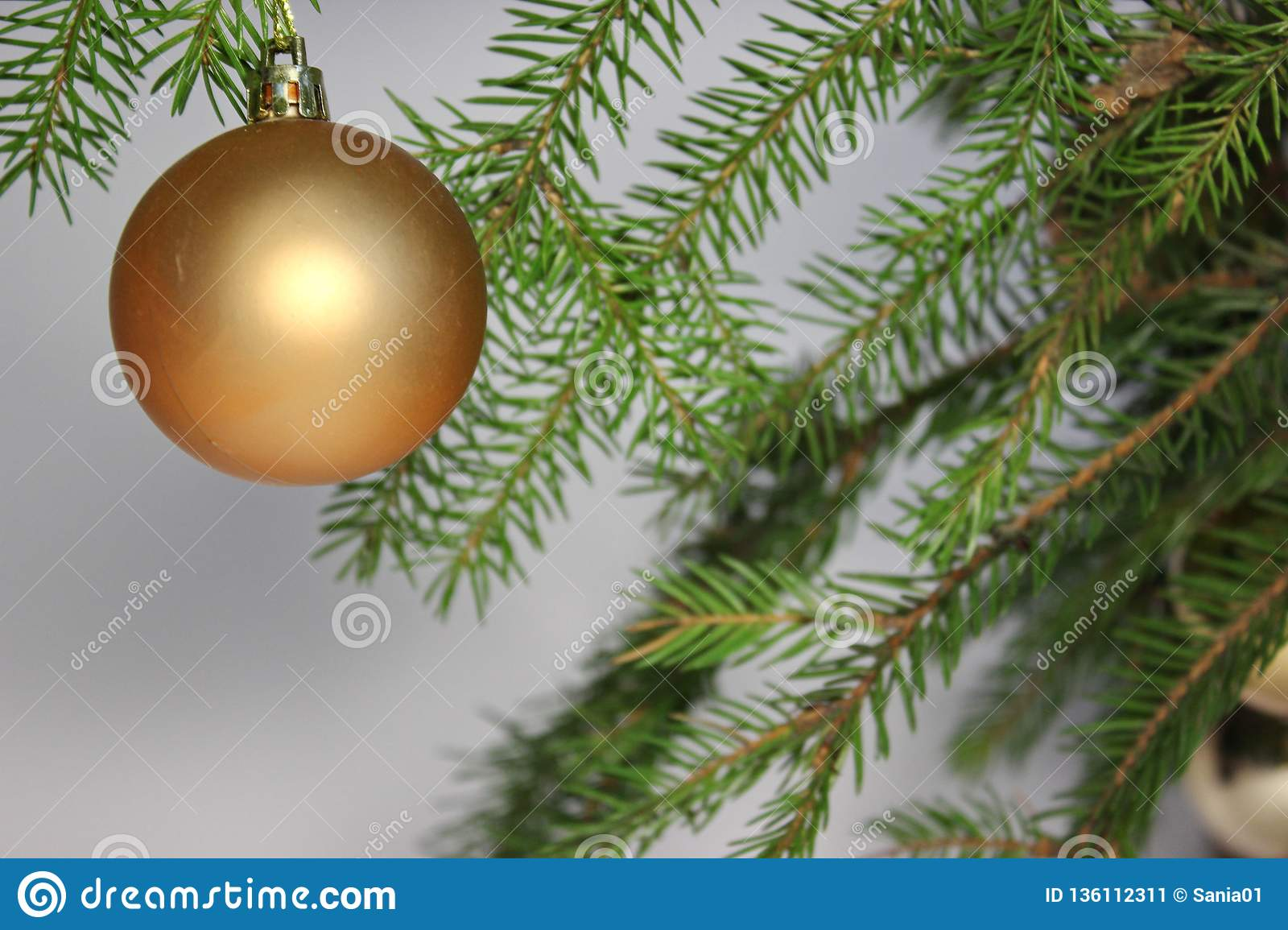 Amber ball on the Christmas tree on a white background. gemstone amber shimmers in the light. orange light. Christmas decorations
