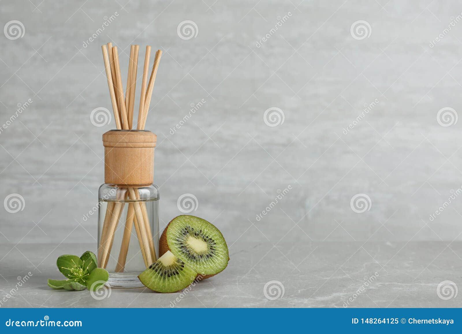 Ambientador y kiwi de lámina aromáticos en la tabla contra fondo gris