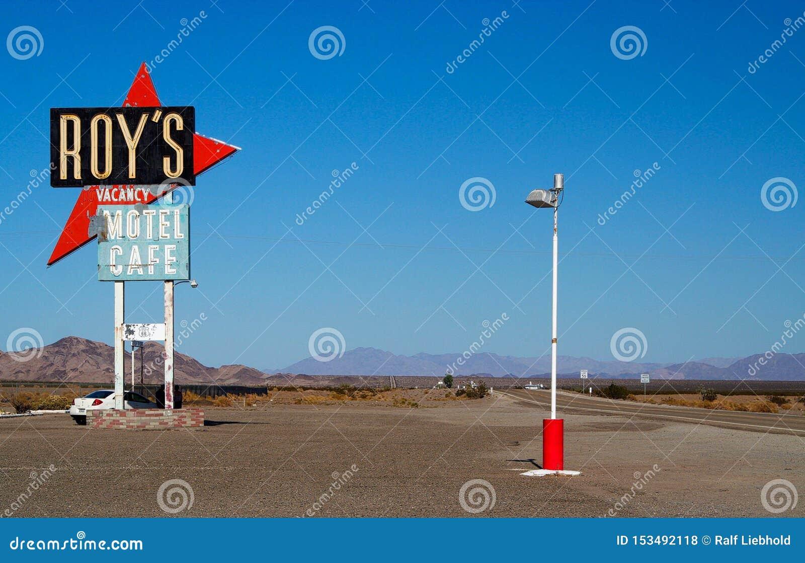 AMBOY CALIFORNIA, U.S.A. - 8 AGOSTO 2009: Segno isolato del motel e del caffè di Roy contro cielo blu a Route 66 con catena montu