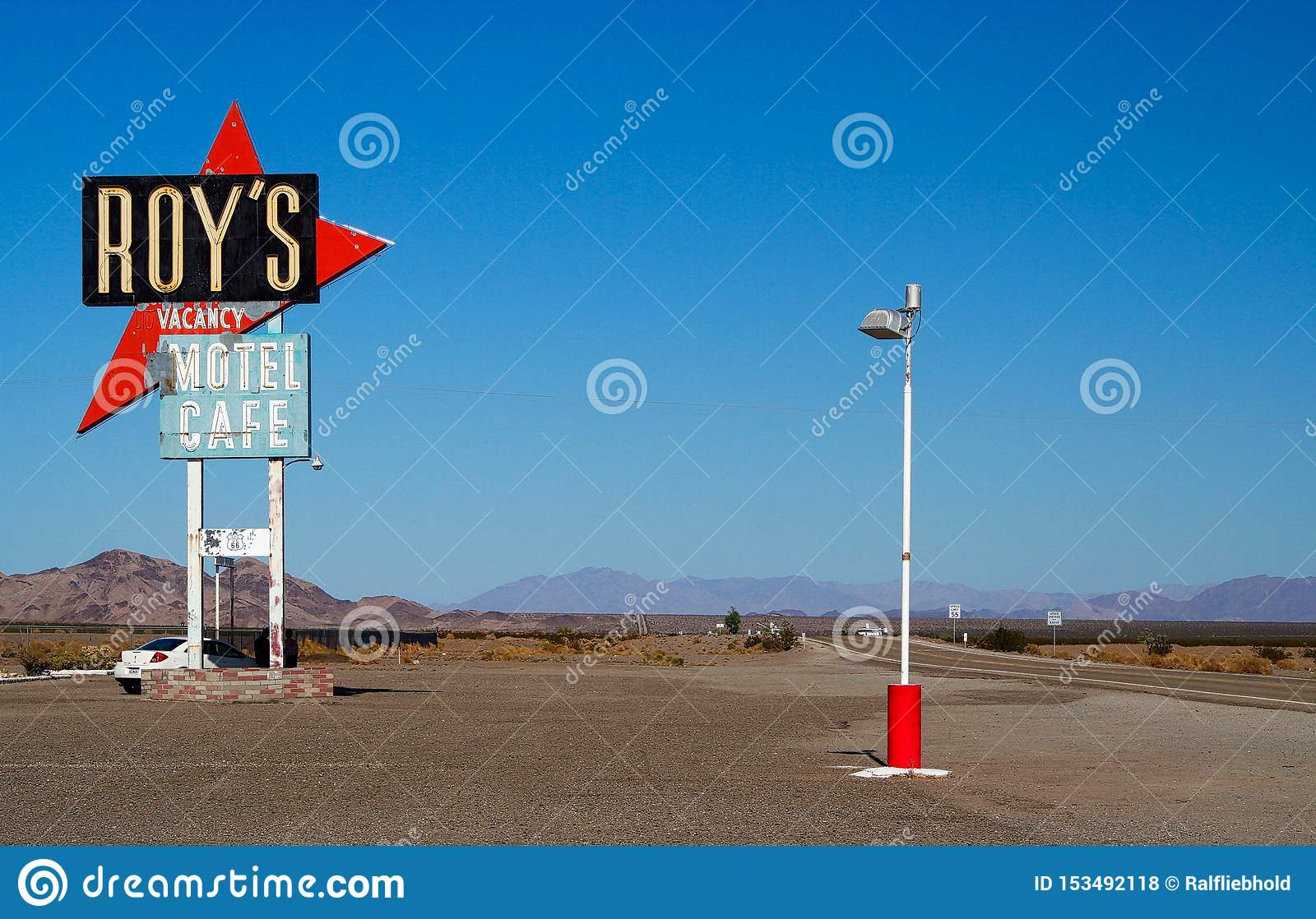 AMBOY CALIFORNIA, USA - AUGUST 8. 2009: Isolated sign of Roy´s Motel and cafe against blue sky at Route 66 with mountain range
