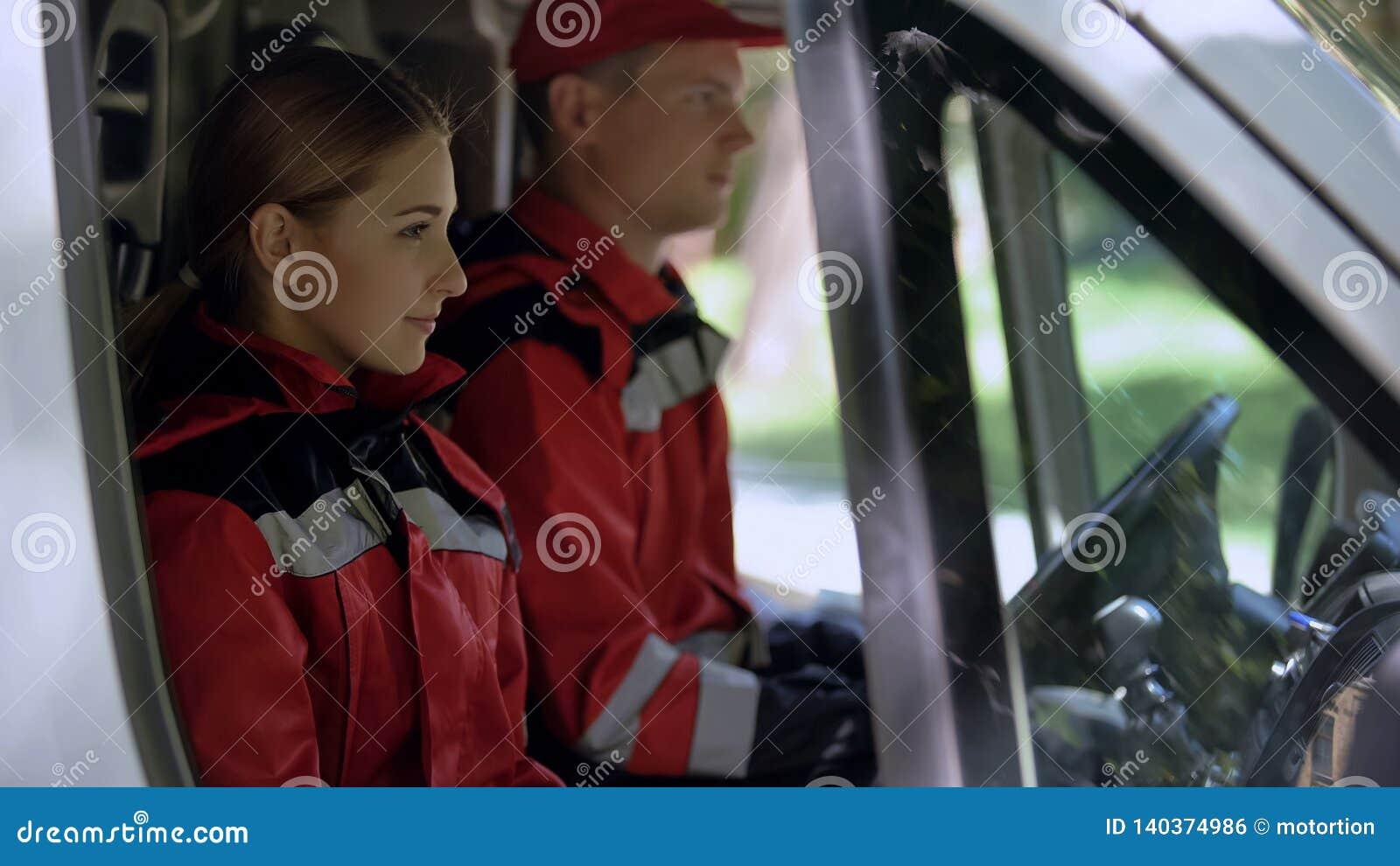 Ambulansbesättning som sitter i transport, yrkesmässig nöd- medicinsk service
