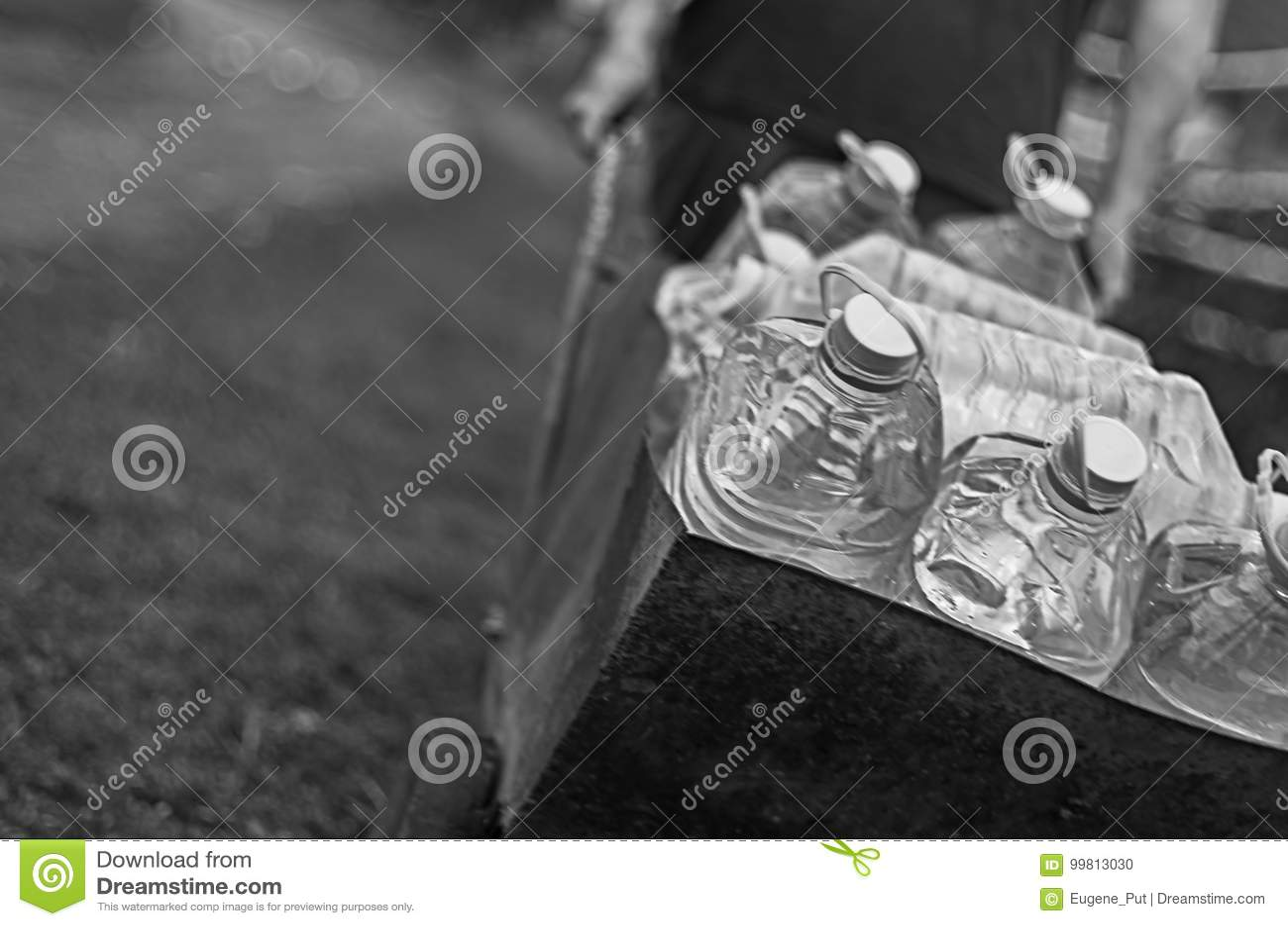 Ameaças da falta da fonte das alterações climáticas e de água O homem branco puxa um carro das garrafas plásticas enchidas com a