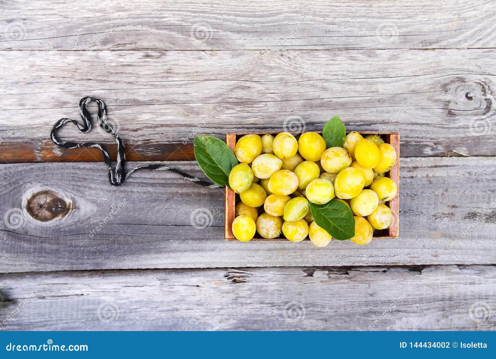Ameixas amarelas frescas Frutos maduros em uma caixa de madeira na grama verde do ver