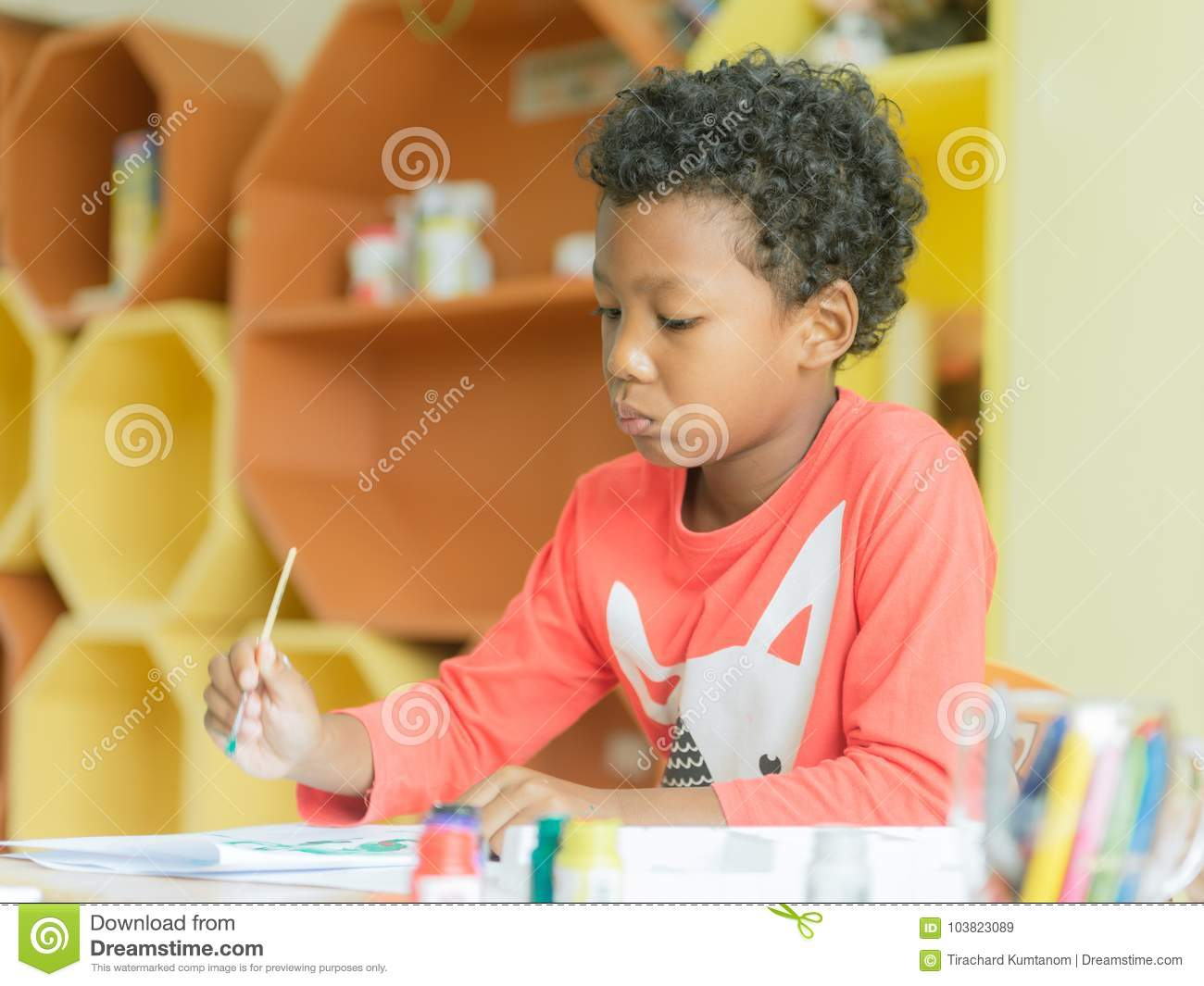 American boy make home wore drawing color pencils in kindergarten classroom, preschool library and kid education concept.