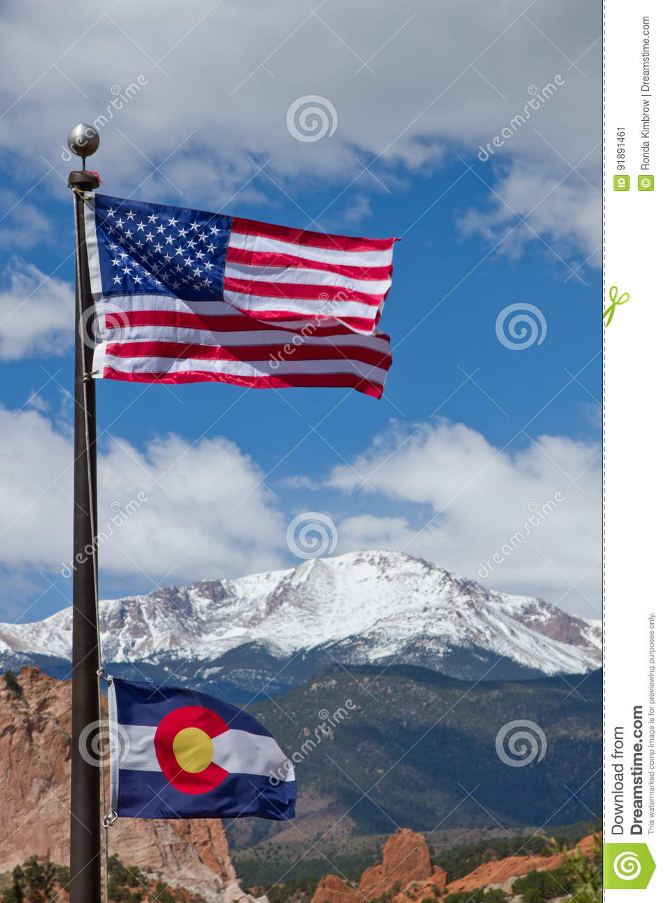 American and Colorado Flag waving in the wind with mountains in