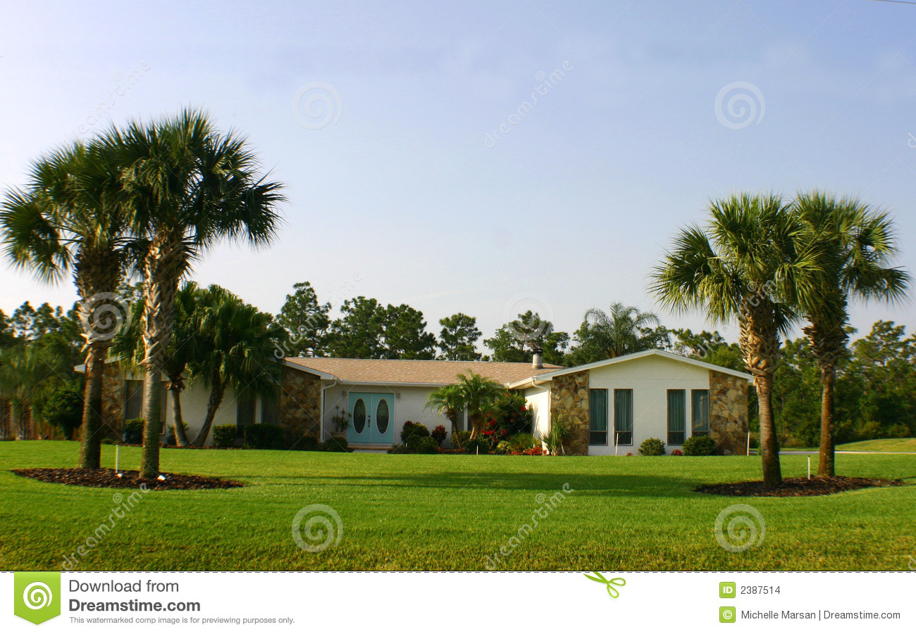 Red entrance door in front of residential house stock photo - American Dream Home With Palm Trees And Blue Doors Stock
