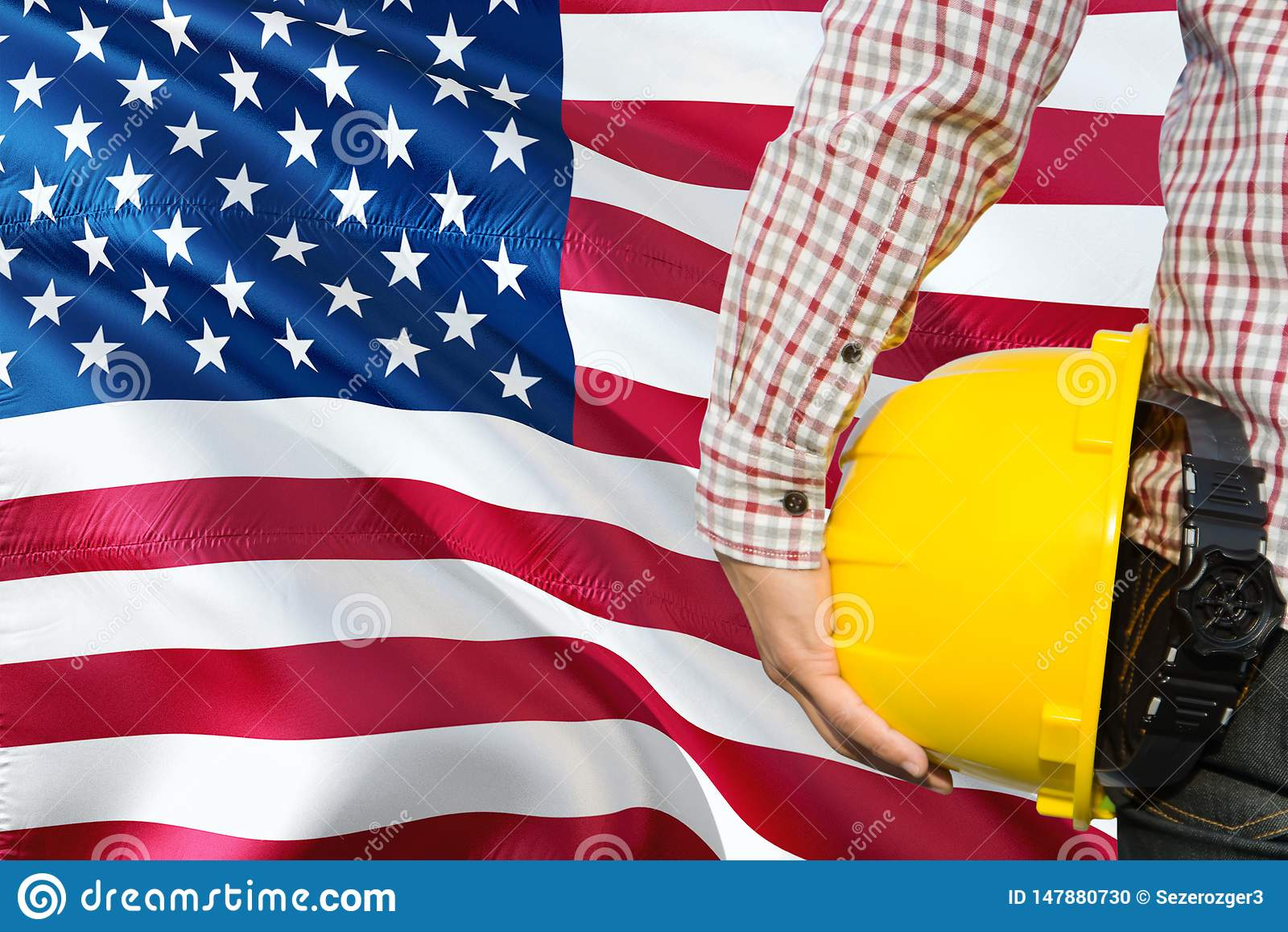 American Engineer is holding yellow safety helmet with waving United States of America flag background. Construction and building