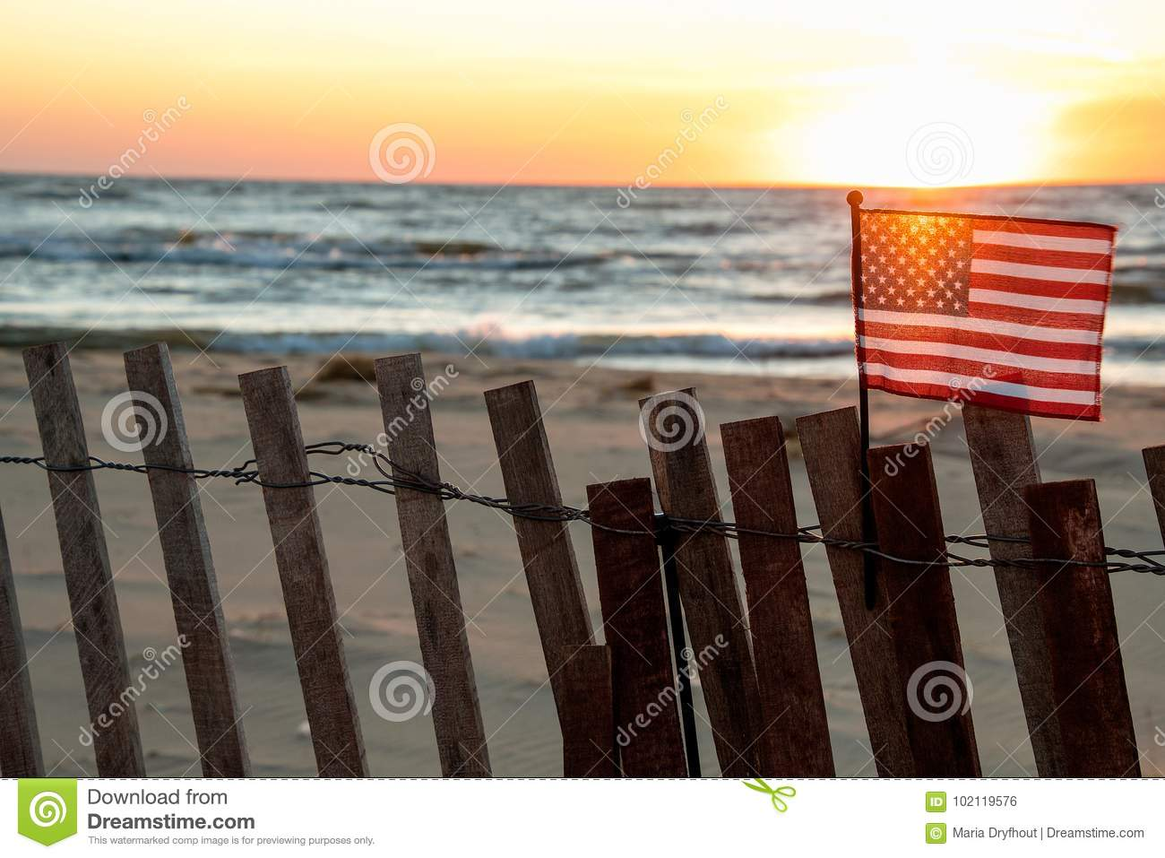 American flag on beach fence with sunset glow