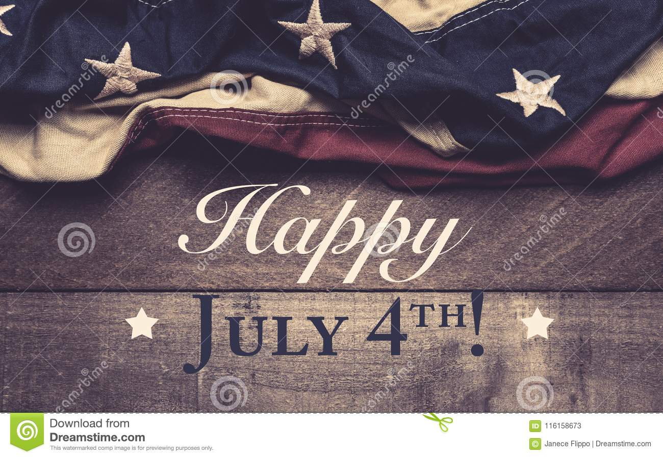 An American Flag Or Bunting On A Wooden Background With July
