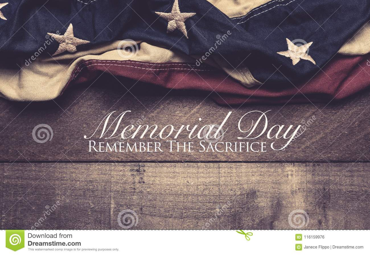 An American flag or bunting on a wooden background with memorial day greeting