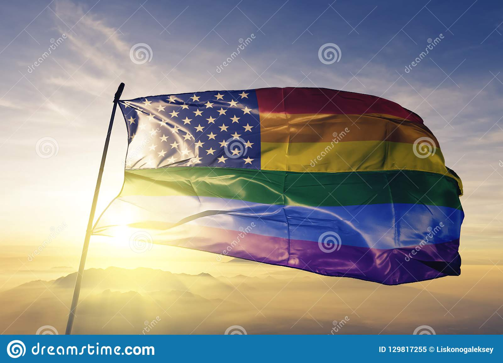 American flag stars gay pride rainbow flag textile cloth fabric waving on the top sunrise mist fog