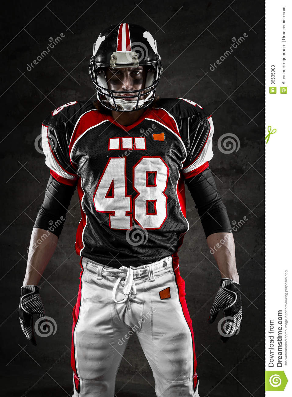 Portrait of american football player looking at camera on dark ...