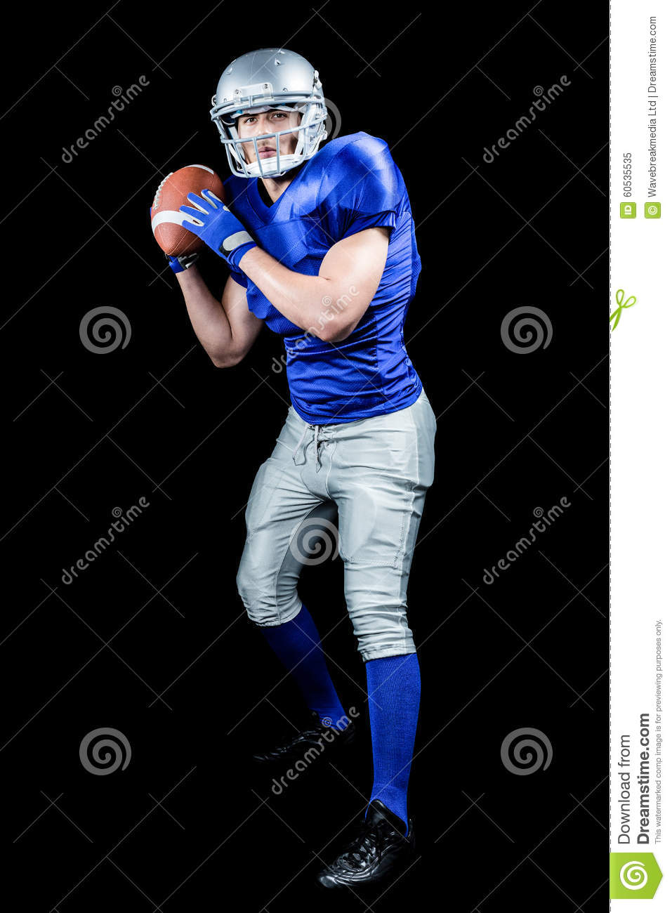 American football player throwing ball over black background