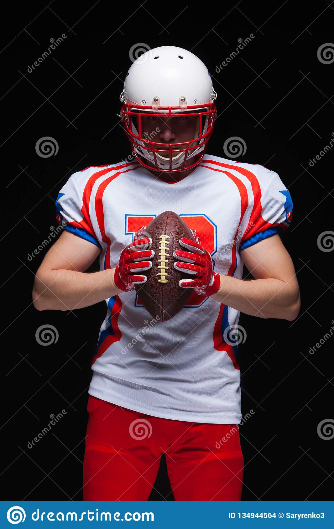 American football player wearing helmet holding ball in front of him on black background