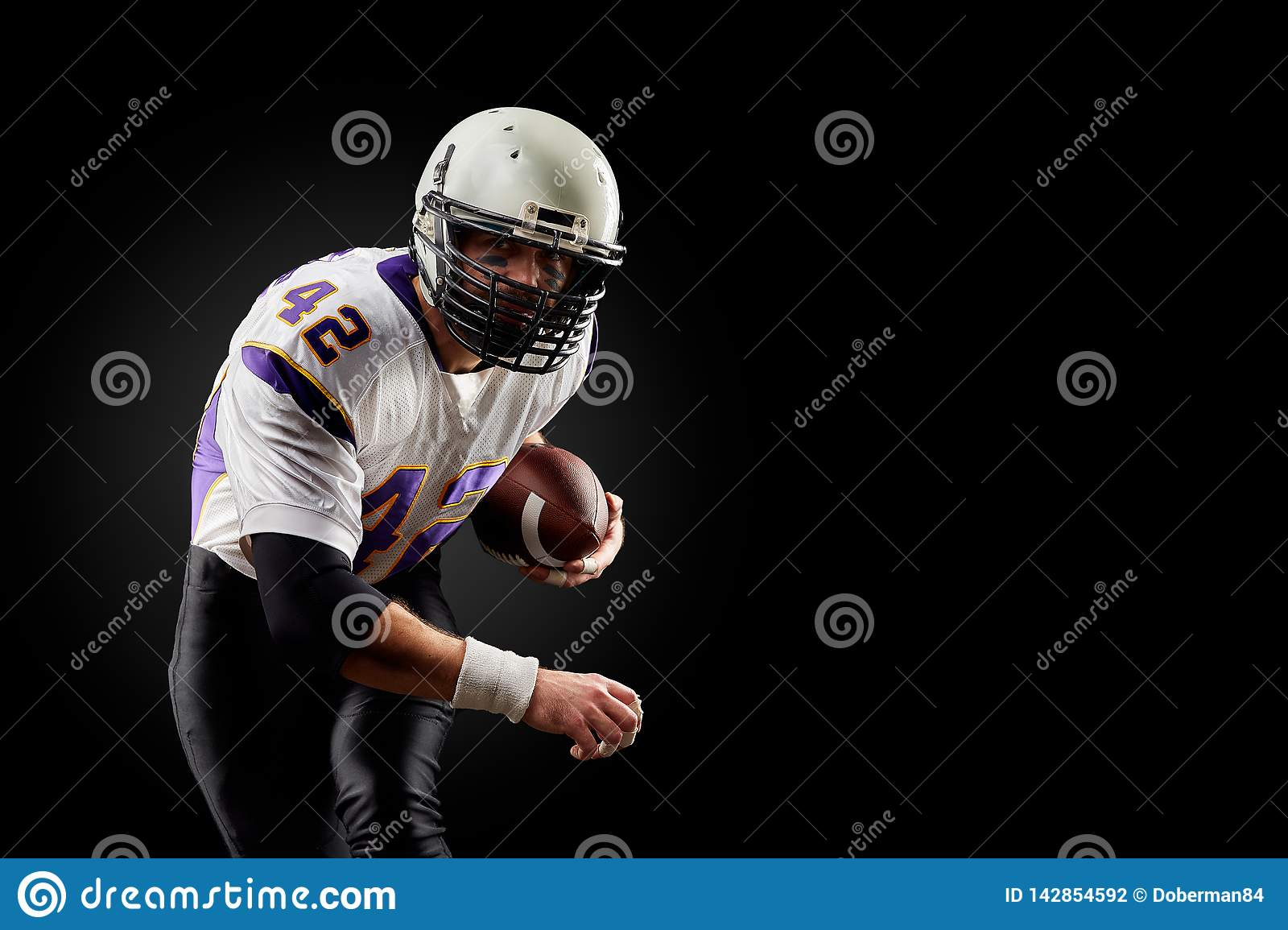 American football sportsman player on black background. Sport concept.