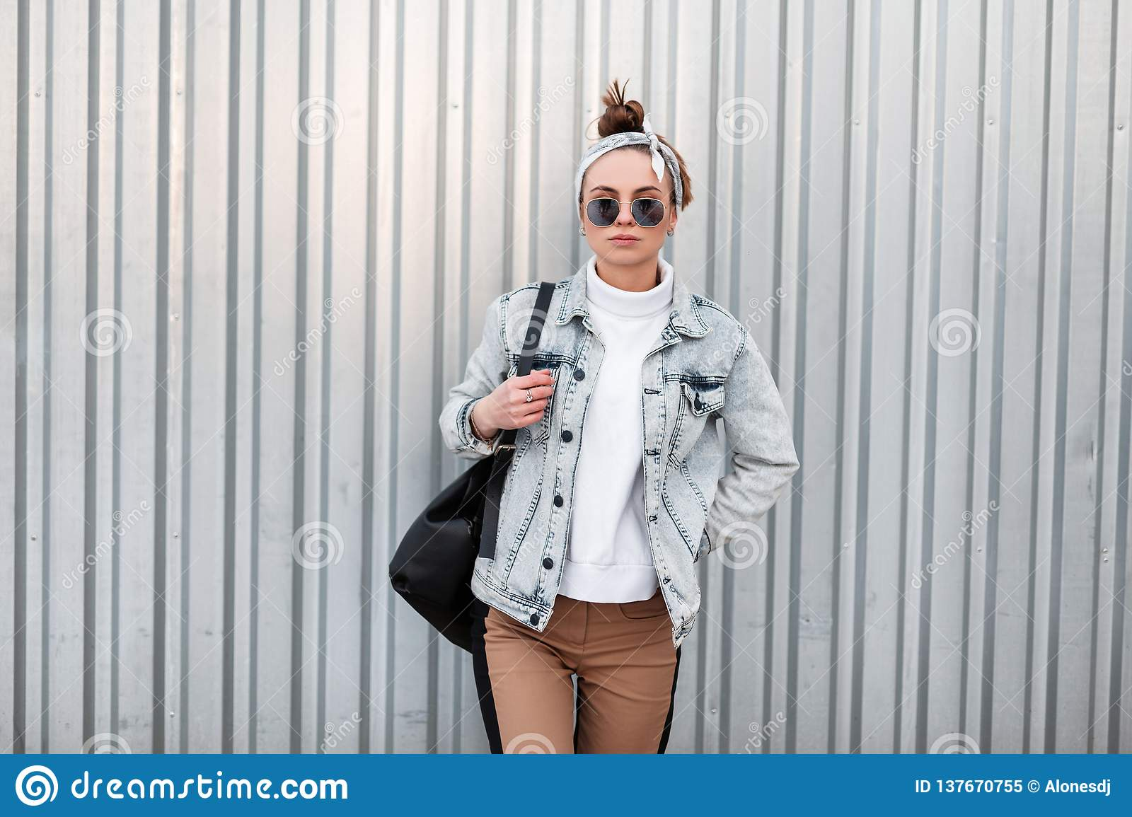 American hipster young woman with a stylish hairstyle in summer denim jackets in trendy pants in a knitted white sweater