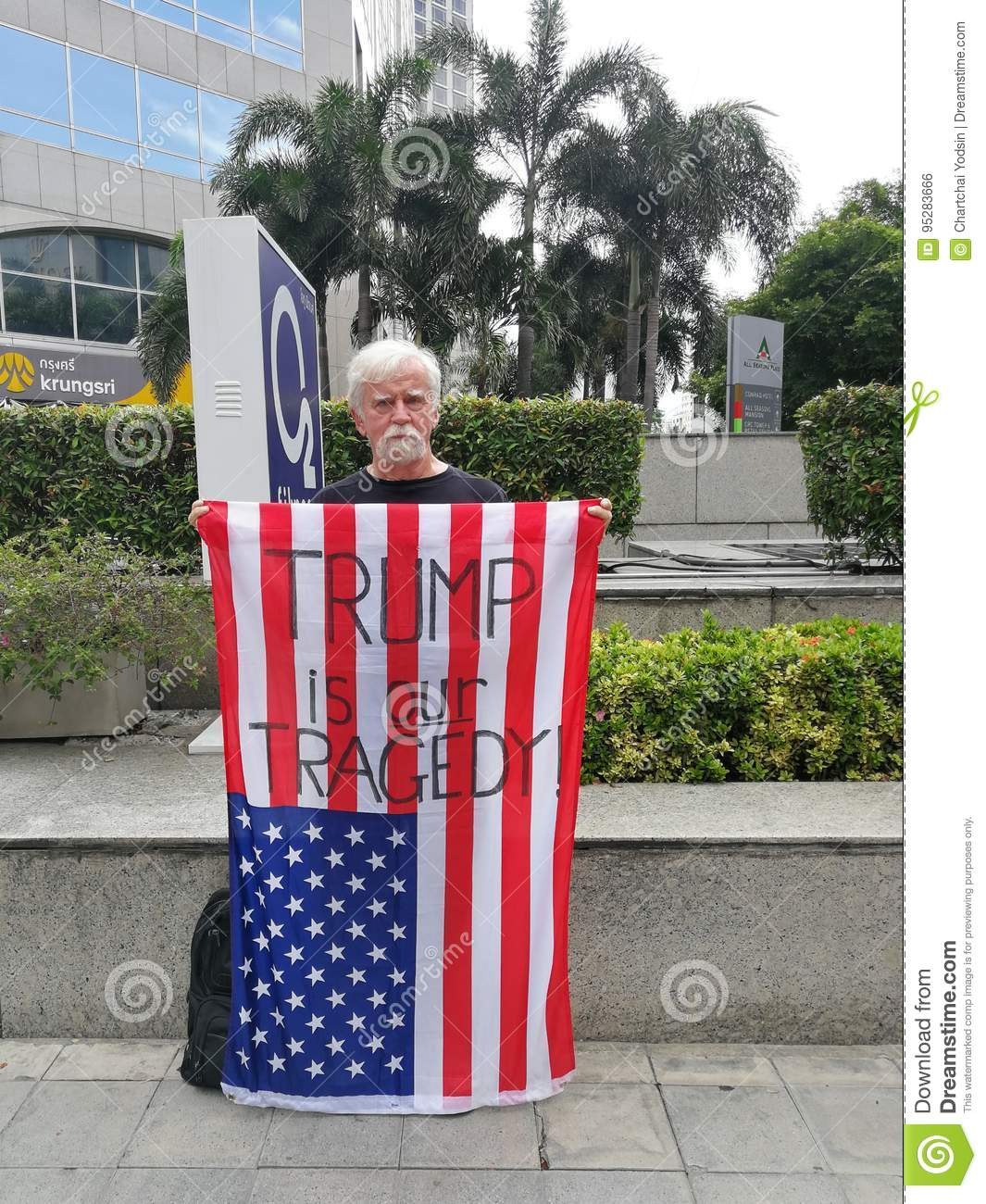 An American man show the American flag with the words `TRUMP IS OUR TRAGEDY.` On the Wireless road near the US embassy in Thailand