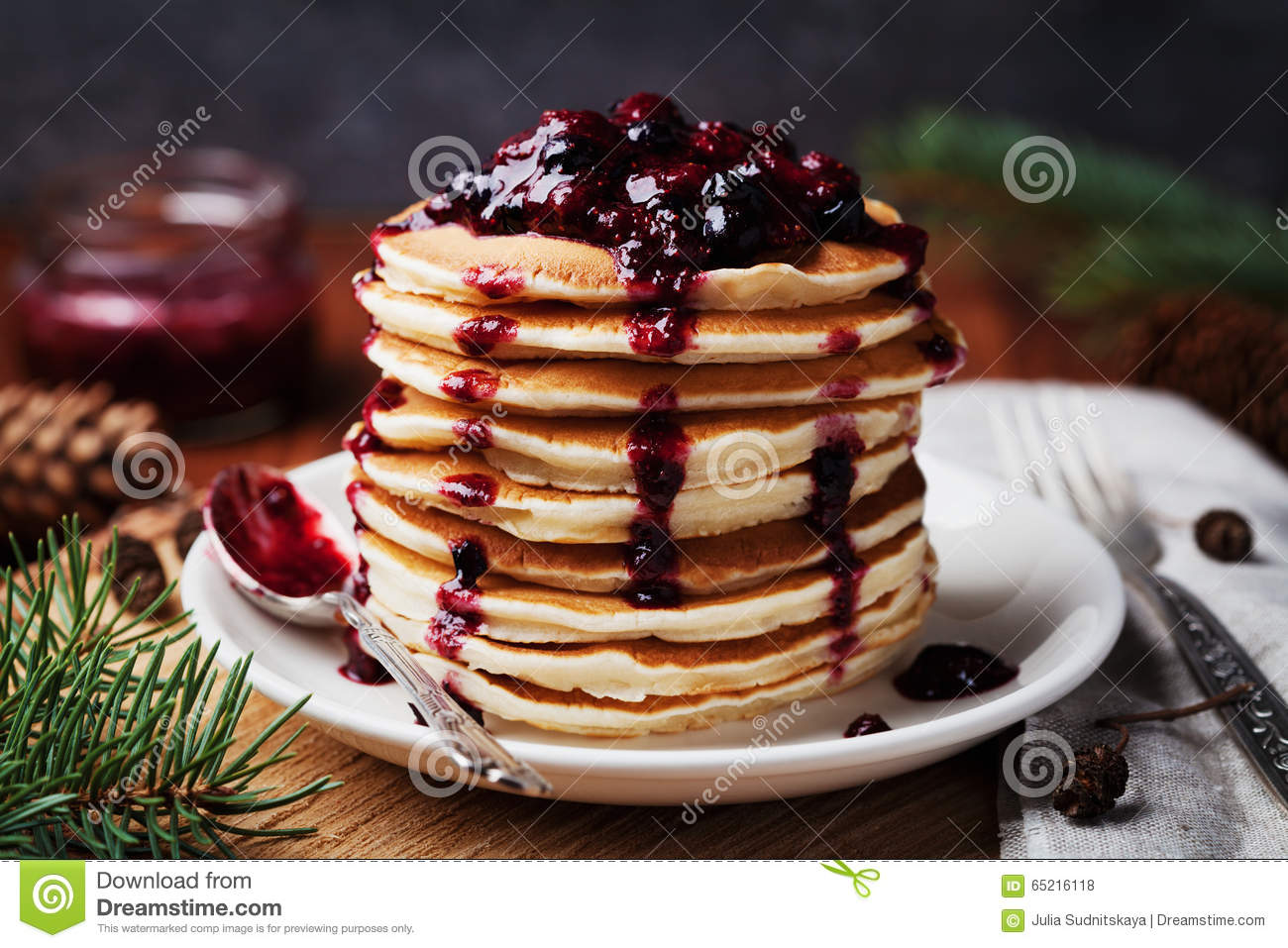 American pancakes or fritters served with strawberry and blueberry jam, delicious dessert for breakfast in winter