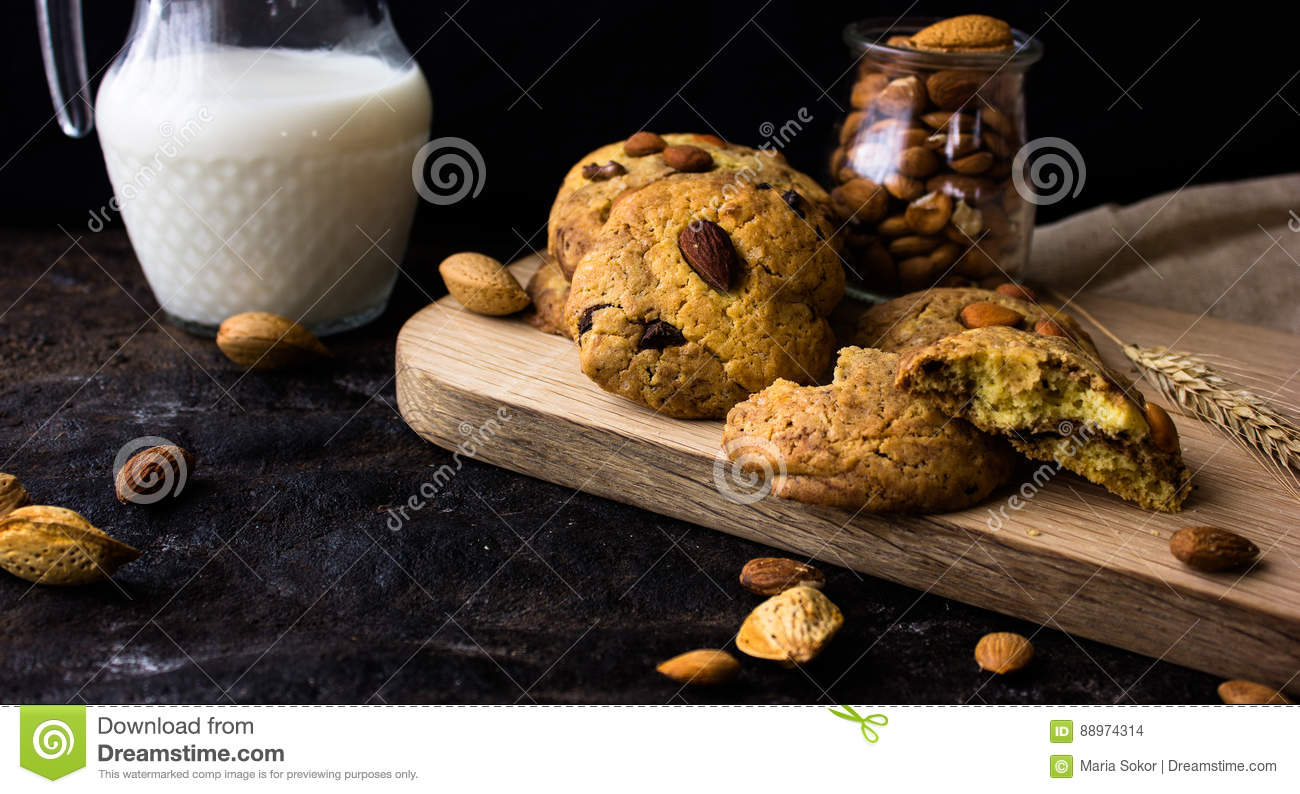 American shortbread cookies with chocolate drops and a jug of milk and almonds. Dark grunge background. Mystical light