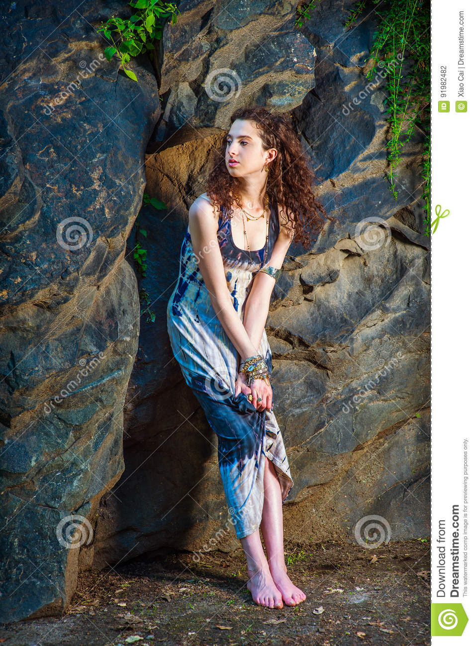 ba47455427a American Teenage Girl Summer Fashion in New York, with curly long hair,  bare feet, wearing patterned long dress, chunky chain bracelet, arm cuff  bracelet, ...