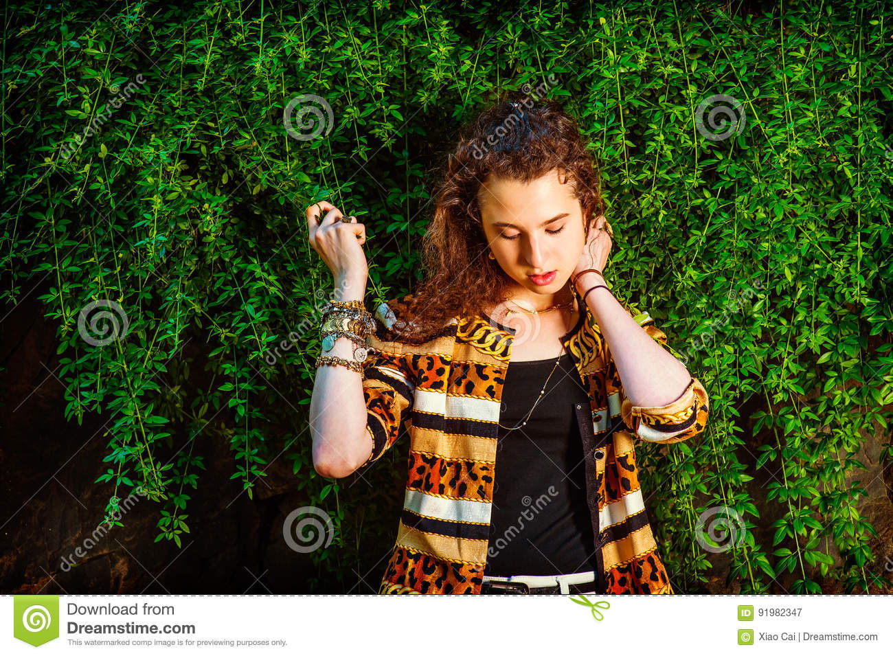 de2db81c36b Dressing in black under wear, patterned fashion jacket, hands holding  leaves, a teenager girl with curly long hair is standing by planted wall,  looking down ...